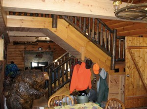 Looking from the kitchen into the living room, the stairs to the loft are in the center of the cabin.